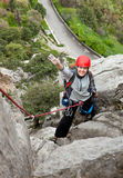 Cheerful female climber ascending a rock Royalty Free Stock Image