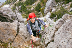 Cheerful female climber ascending a rock Royalty Free Stock Photo