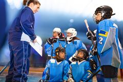 Female coach showing game plan to ice hockey team. Cheerful female coach showing clipboard with game plan to ice hockey team stock photography