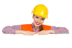 Cheerful Female Construction Worker Leans On A Poster Stock Photos