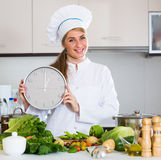 Cheerful female cook with clock and vegetables in kitchen. Smiling woman in chef cap holding clock as preparing vegetables Royalty Free Stock Photography