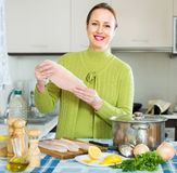 Cheerful female cooking fish Stock Photos
