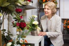 Cheerful female customer choosing flowers Stock Photo