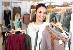 Cheerful female customer selecting new garments Royalty Free Stock Photos