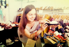 Cheerful female customer selecting shoes in footgear center. Portrait of cheerful female customer selecting shoes in footgear center Royalty Free Stock Photography
