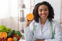 Free Cheerful Female Dietician Holding Fresh Orange Half Stock Photos - 181440263