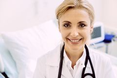 Cheerful female doctor beaming while looking into camera Royalty Free Stock Photos