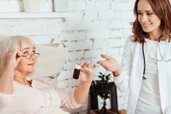 Cheerful female doctor visiting her patient at home royalty free stock photo