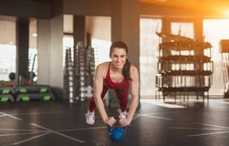 Cheerful female doing plank on kettlebell royalty free stock images