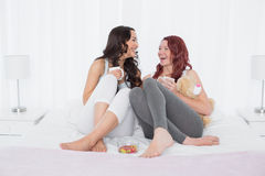 Cheerful female friends chatting over coffee in bed. Cheerful relaxed female friends chatting over coffee in bed at home Stock Image