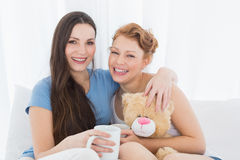 Cheerful female friends with coffee cups in bed Stock Photos