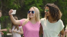 Cheerful female friends dancing to music at summer party, taking selfie on phone. Stock footage stock footage