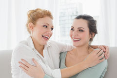 Cheerful female friends embracing in living room Royalty Free Stock Image