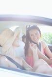 Cheerful female friends enjoying road trip in car Royalty Free Stock Photo
