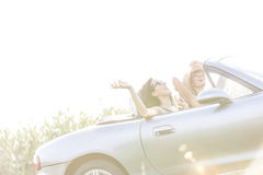 Cheerful female friends enjoying road trip in convertible on sunny day Royalty Free Stock Photos