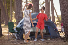 Cheerful female friends enjoying together by tent Royalty Free Stock Photo