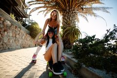 Cheerful female friends skating outdoors. Cheerful female friends playing on the skateboard outdoors. Woman pushing a friend on a skateboard. Summer vacation Royalty Free Stock Image