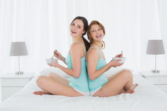 Cheerful female friends with salad bowls sitting on bed Stock Image