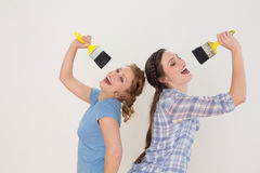 Cheerful female friends singing into paintbrushes Royalty Free Stock Photos