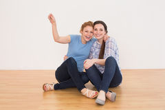 Cheerful female friends sitting in a new house Royalty Free Stock Image
