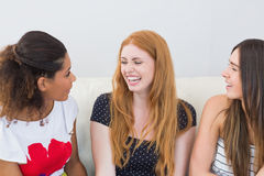 Cheerful female friends sitting on sofa at home Stock Image