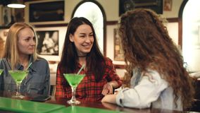 Cheerful female friends are socializing in fancy bar. Attractive women are chatting, laughing and touching cocktail stock footage