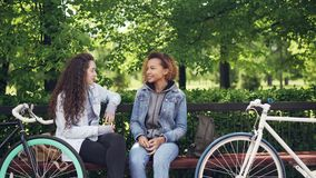 Cheerful female friends are talking discussing news sitting on bench in town park with bikes and bags visible. People. Are walking in background along paths stock footage