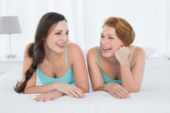 Cheerful female friends in teal tank tops lying in bed Stock Images