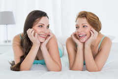 Cheerful female friends in teal tank tops lying in bed Stock Photo