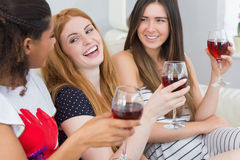 Cheerful female friends with wine glasses enjoying a conversation Stock Photos