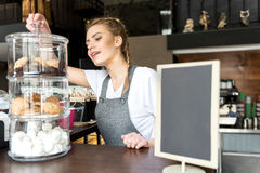 Cheerful female getting cakes in cafe Stock Images