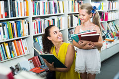 Cheerful female with girl in bookstore. Young cheerful female with girl in school age looking in open book in bookstore stock photo