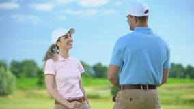Cheerful female golfer with club giving high-five sport coach, teamwork concept. Stock footage stock video footage