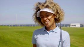 Cheerful female golfer walking with golf club stock video