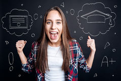 Cheerful female graduate student having a graduation party. Start new life. Pleasant overjoyed delighted graduate student celebrating graduation and expressing Stock Image