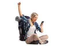 Cheerful female hiker sitting on the ground and looking at a mob Royalty Free Stock Image