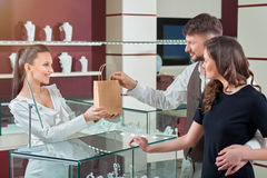 Free Cheerful Female Jeweler Handing Purchase In A Shopping Bag To He Royalty Free Stock Photos - 86357368
