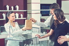 Cheerful female jeweler handing purchase in a shopping bag to he. Service at the shop. Beautiful happy loving couple receiving their purchase in a shopping bag stock photography