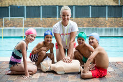 Cheerful Female Lifeguard And Children During Rescue Training Royalty Free Stock Photos