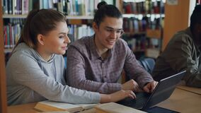 Cheerful female and male college students working on laptop together while sitting at table at university library with. Cheerful female and male college students stock footage