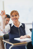 Cheerful female mature student raising her hand Stock Photography