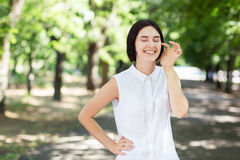 A cheerful female on a natural background. A beautiful laughing girl touching her face. A cute lady having fun in a summer park. Royalty Free Stock Photography