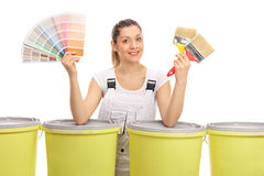 Cheerful female painter with color swatch and paintbrushes. Cheerful female painter with a color swatch and paintbrushes behind color buckets isolated on white Royalty Free Stock Images