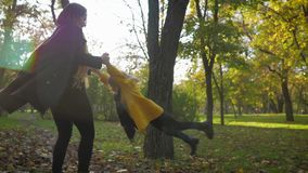 Cheerful female parent plays with her charming daughter twists her hands in autumn park while walking outdoors