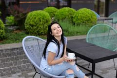 Cheerful female person sitting in chair at cafe near green plants and drinking coffee. Concept of leisure time and resting Stock Photography