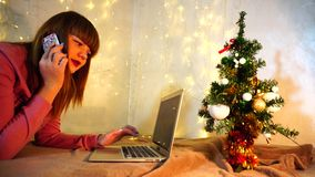 Cheerful female person talking on phone and typing message on laptop. Happy girl calling boyfriend to congratulate on Christmas. Gladden woman writing message stock video footage
