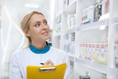 Cheerful female pharmacist working at the drugstore stock image