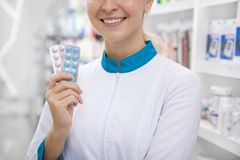 Cheerful female pharmacist working at the drugstore royalty free stock images