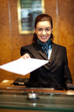 Cheerful female receptionist offering Stock Image