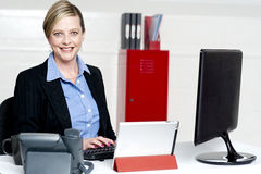 Cheerful female secretary typing document Royalty Free Stock Photography